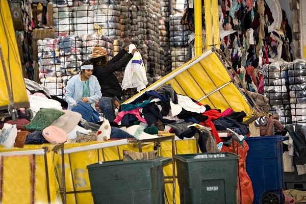 Workers sorting through used clothing for recycling. Photo courtesy of Secondary Materials and Recycled Textiles (SMART) 2013.