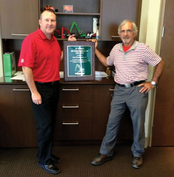 Top Lift's David Shea (L) and Emidio Greco proudly display their 10 year partnership award from Sennebogen.