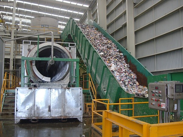The inbound feed line to the pulping system at a paper mill, with screen. Cartons arrive in a bale, which is broken apart, and then move onto the in-feed conveyor, and are dumped into a pulper.