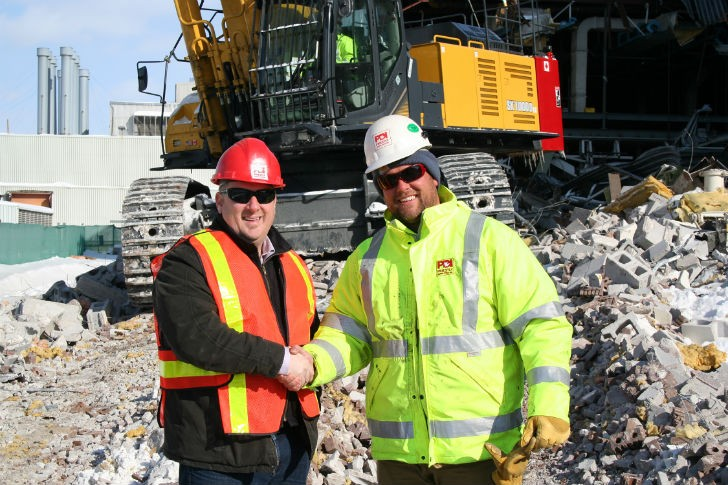 Aaron Hopkins, of Robert Green Equipment Sales Ltd. and Ryan Priestly, of Priestly Demolition Inc. shaking hands on the sale of the KOBELCO SK1000.