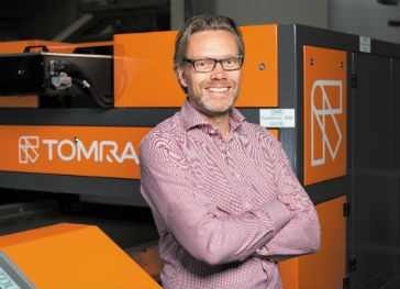 Tom L. Eng, VP and Head of TOMRA Sorting Recycling in front of a rebranded machine: The prominent orange remains, new is the TOMRA logo.