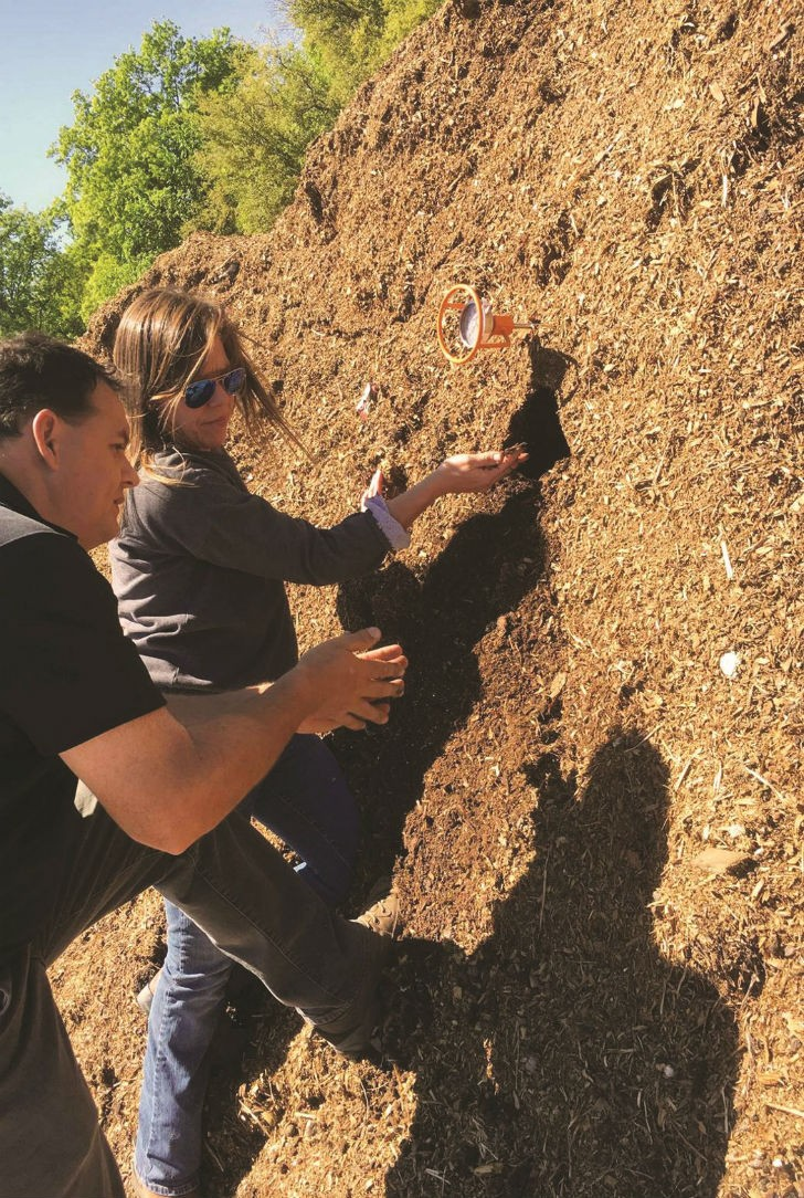 Darren Midlane, CTO of Harvest Quest, with Heather Mayer from Mayer Materials examining the quality of their compost.