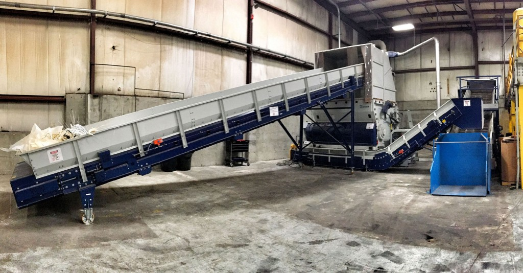 Tailor-made for Winco Plastics: Lindner's re-grinding line includes a conveyor belt (left) to feed the Micromat 2500 Pre-Shredder, followed by two successive conveying belts with a metal detector, used to feed a Lindner LG 1500-800 grinder (on the right behind the Gaylord dumper).