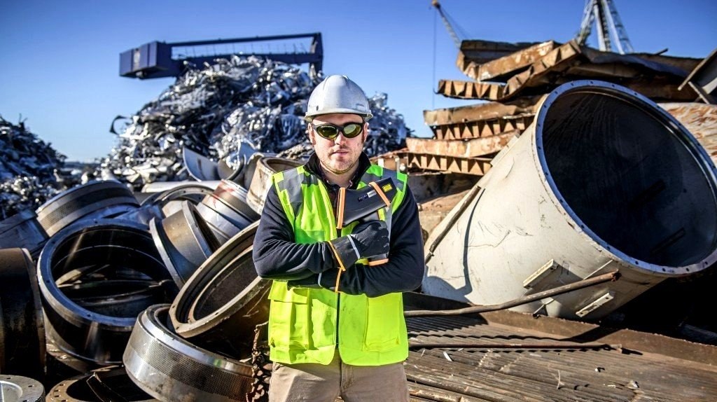 Man stands in front of a pile of metal scrap in a recycling yard.
