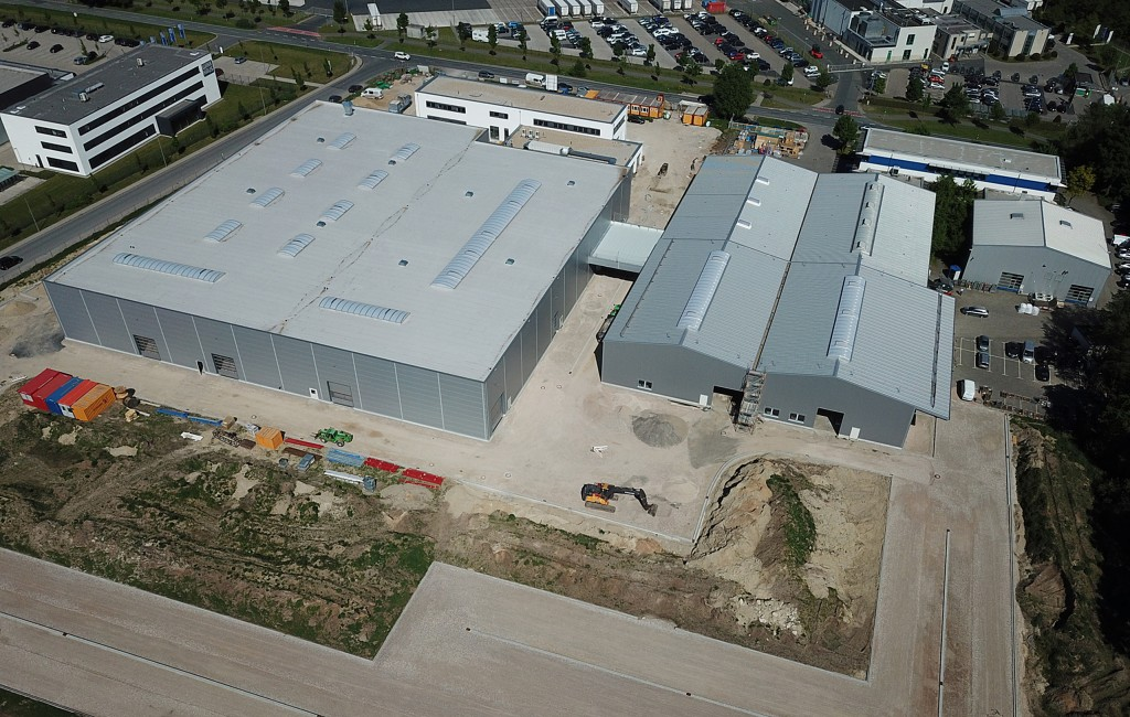 An aerial view of the extensive expansion of the Nordson BKG GmbH facility in Münster is apparent from this aerial view. The large gray building at left of centre is an entirely new manufacturing centre for BKG pelletizers and melt delivery systems. The gray building at right of centre also houses manufacturing operations, and of its four sections, the front two are entirely new. The white buildings at the rear of these two large buildings are office structures, the one at left being new as well.