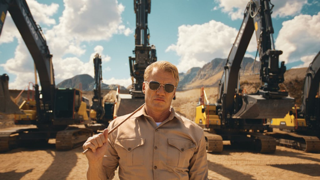 """During a series of extraordinary stunts, the Volvo excavators are seen pulling Dolph Lundgren atop a huge concrete block across an unknown desert location, flipping gigantic tires across a muddy track and taking part in what is thought to be the world's first ever excavator pull-up – fulfilling the film's final message that they really are """"excavators for any challenge."""""""