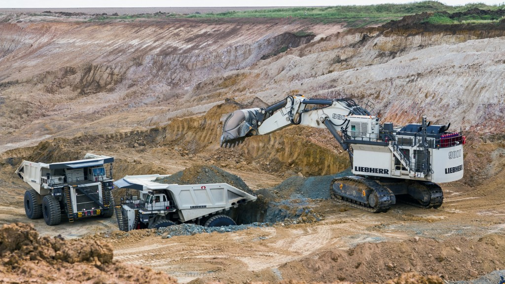 Two Liebherr T282 mining trucks and an R 9800 mining excavator at work.