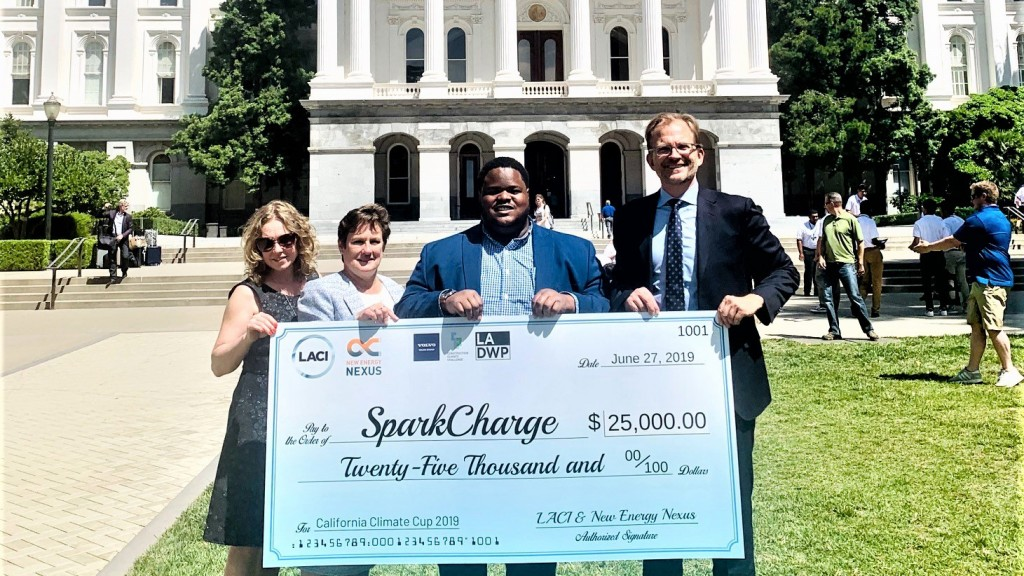 three people accept an award with big cheque