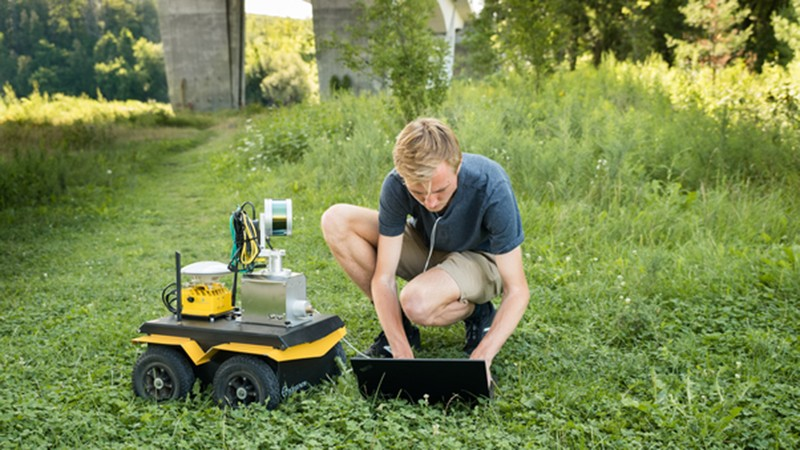 Stephen Phillips, a PhD student at the University of Waterloo, works with a robotic ground vehicle used in research on automating bridge inspections.