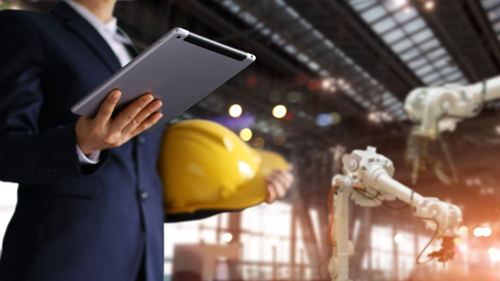 Man holding a tablet with a construction hat in hand