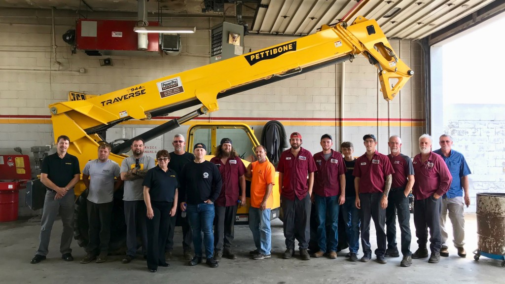 a group of men stand in front of a telehandler