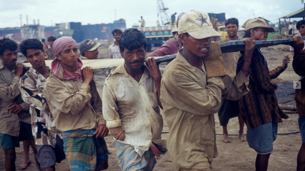 Bangladeshi workers scrapping imported ships on the beach. Shipowners take pains to circumvent Basel Convention controls because the ships contain asbestos, heavy metals, and flammable gasses and oils, contaminating the beaches and causing death and occupational disease of the workforce. Copyright Greenpeace 2006.