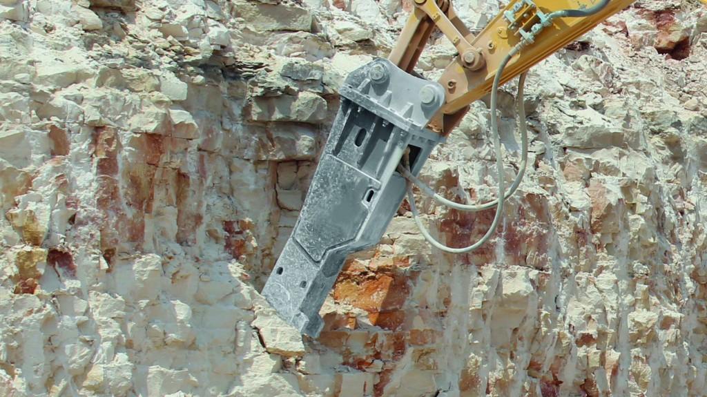 hydraulic breaker breaking into a wall of rock