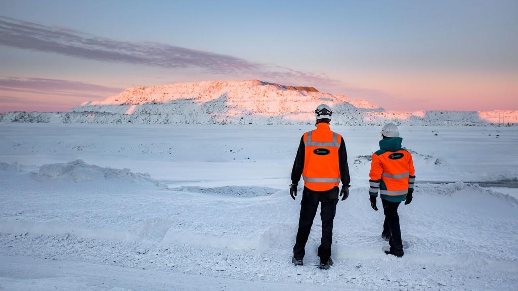 two metso workers survey snowy landscape