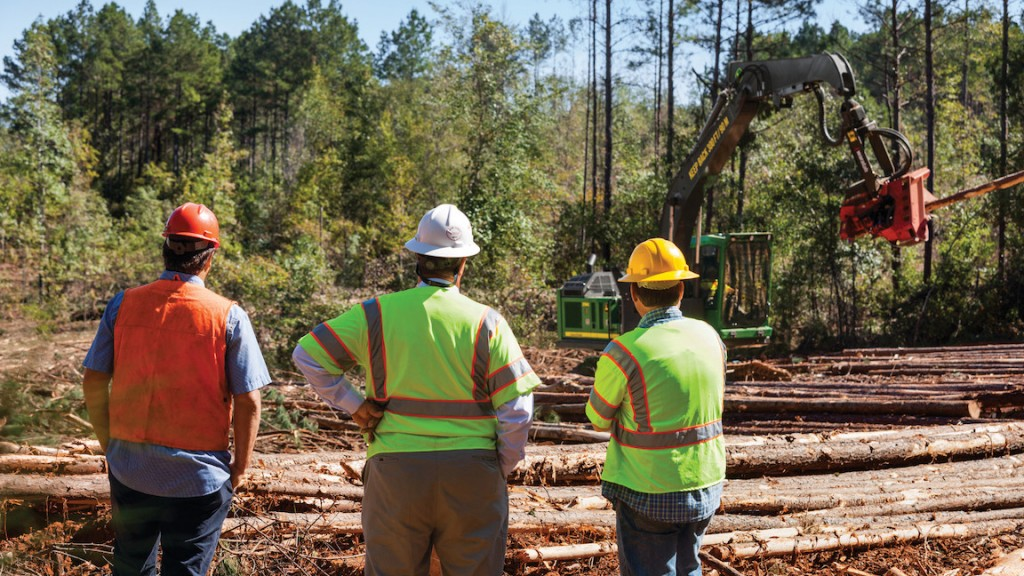 Forestry workers look on as logging machine picks up log