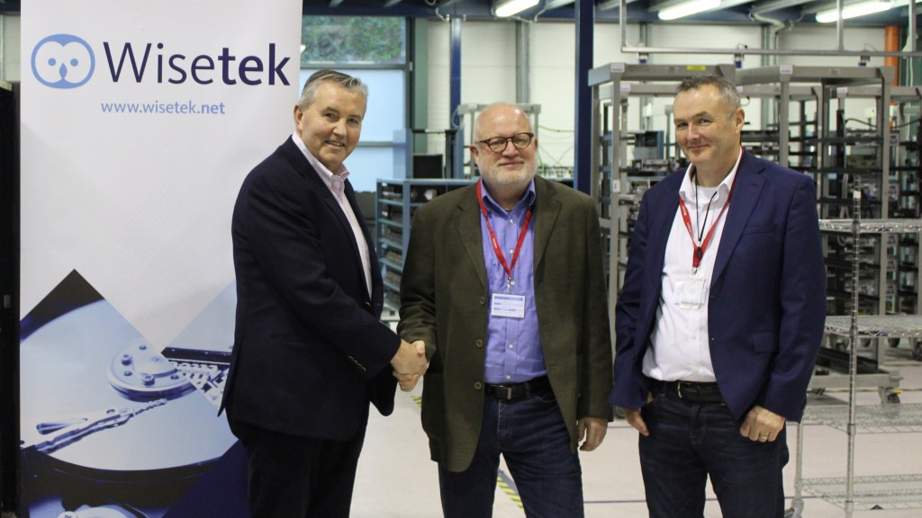 three men shake hands in front of Wisetek logo
