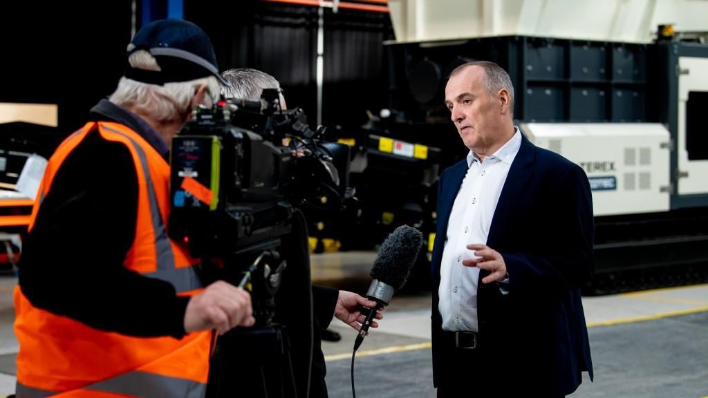 man being interviewed near terex machine