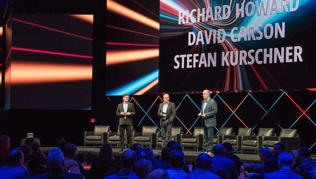 three men address a crowd