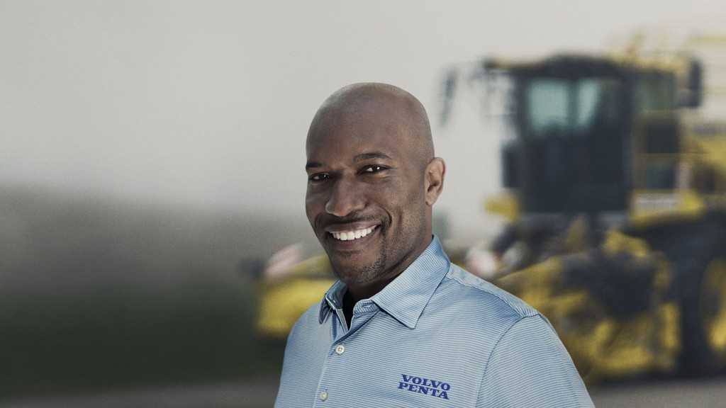 Volvo worker smiles in front of machine