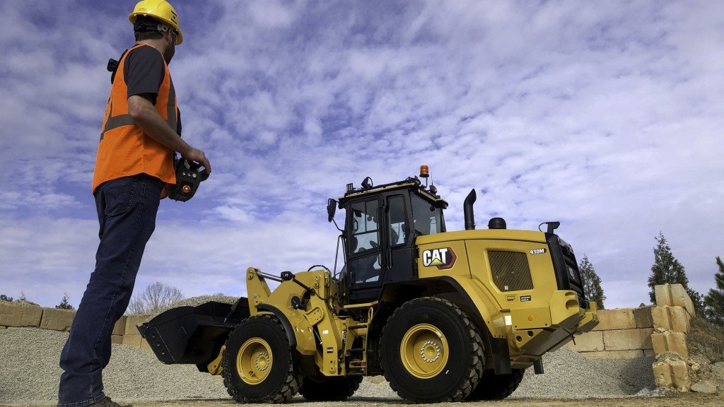 man performs action on cat command to control wheel loader