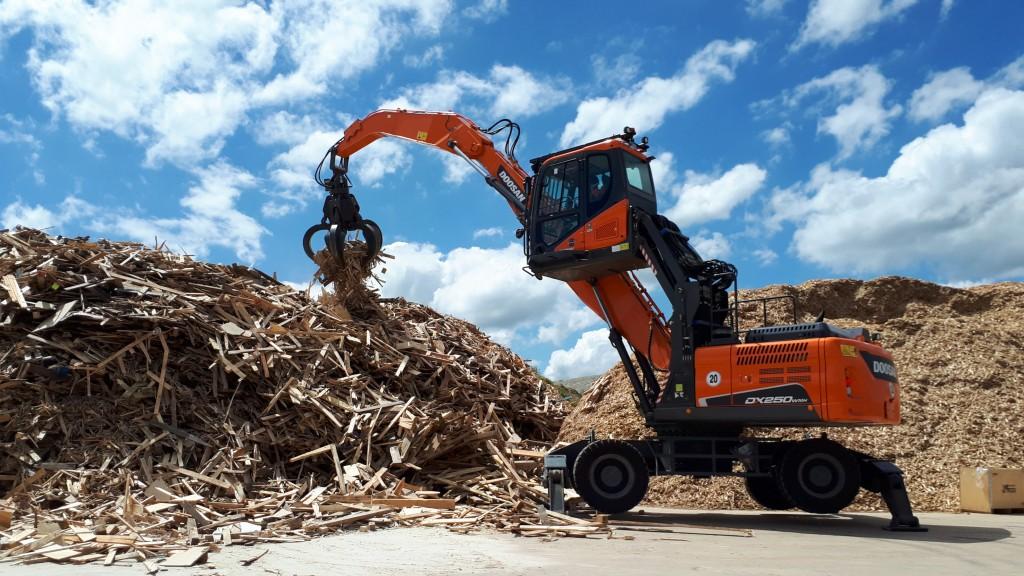 Doosan DX250WMH-5 wheel material handler at waste wood pile