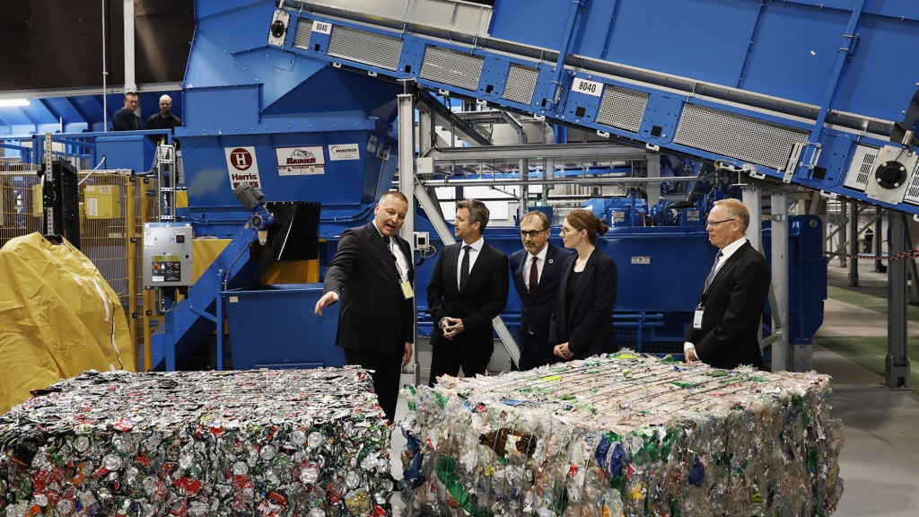 a group of people in front of Stadler machinery and blocks of plastic