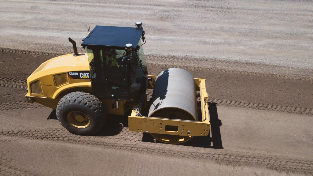 Caterpillar soil compactor working on a road