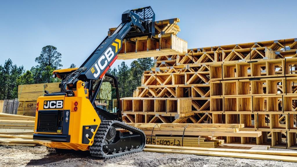 A JCB teleskid handles building materials on a jobsite