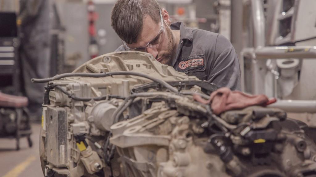 A daimler mechanic works on a truck part