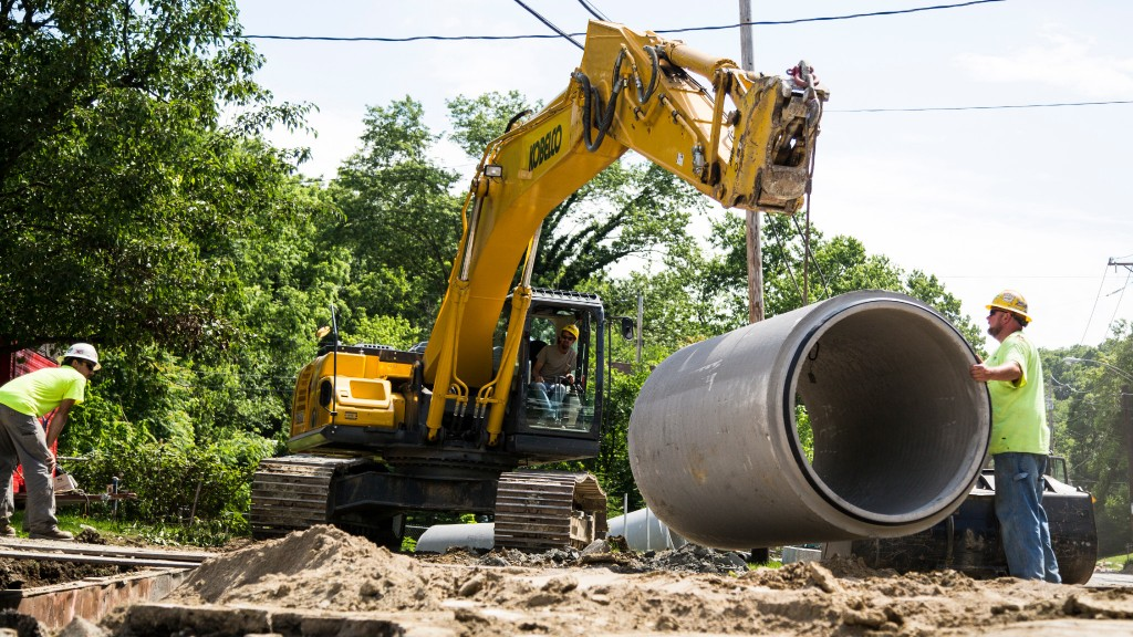 An excavator lifting a concrete sewer pipe