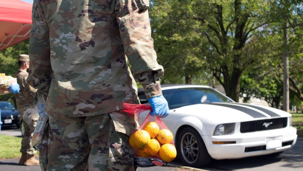 national guard worker stands with a bag of oranges