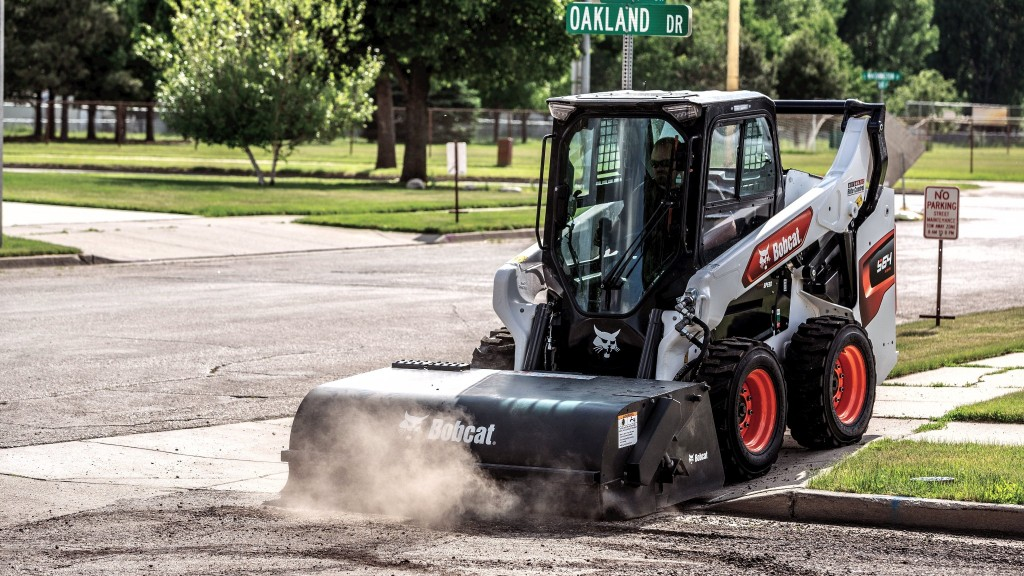 A Bobcat skid-steer loader with a sweeper attachment.