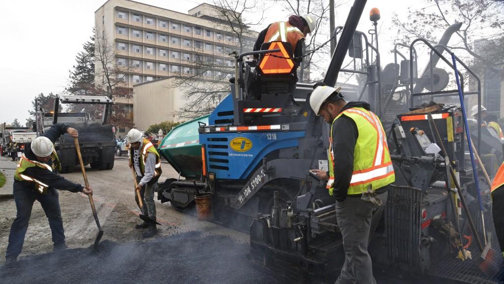 Paving crew working around asphalt paver