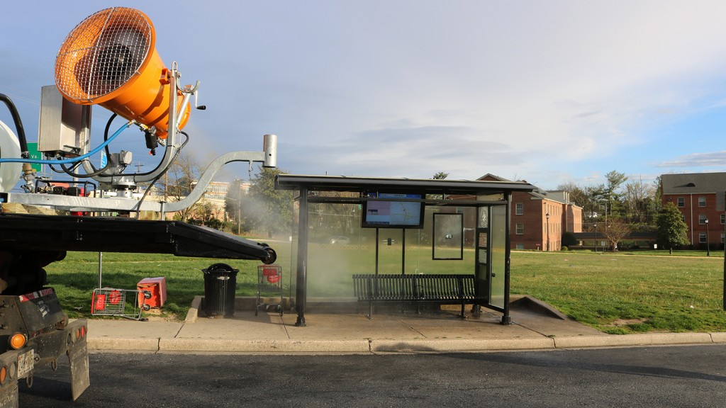 a dustboss atomized mist machine mists a road and a bus stop