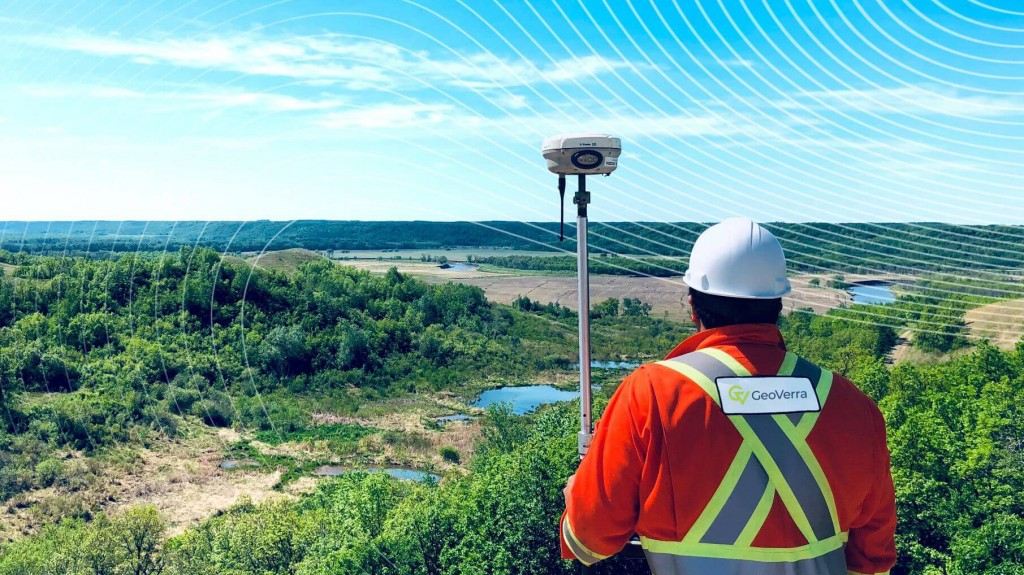 Geoverra worker using geospatial equipment looking over a valley