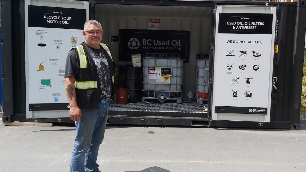 BC Used Oil worker next to a recycling centre