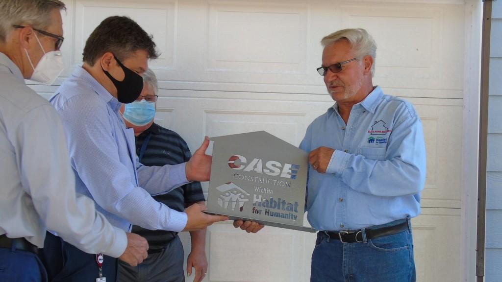 Men in masks accept habitat for humanity award for case construction