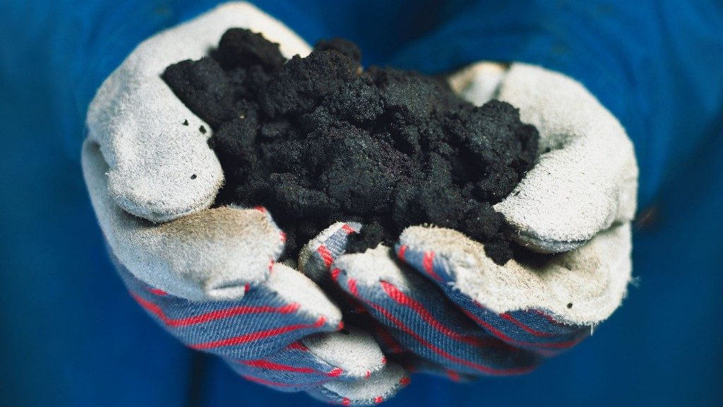 Hands holding sand containing bitumen