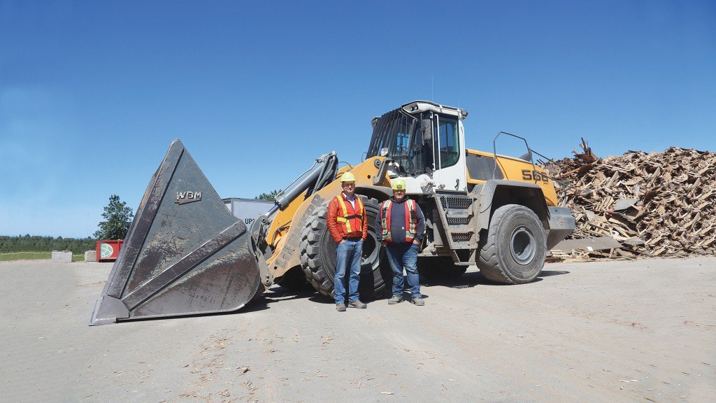 Christian Dietrich, GM of Ecowaste's waste management division, and Shaun Salmon, site foreman, at the waste wood pile with their 566 wheel loader.
