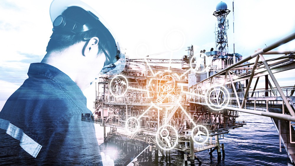 oil rig worker using a tablet near an oil rig
