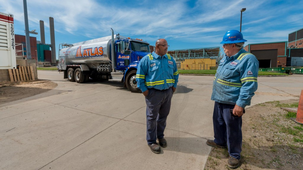 two men standing in front of Atlas Oil truck