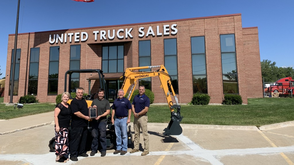people stand in front of Hyundai machine and united truck sales facility