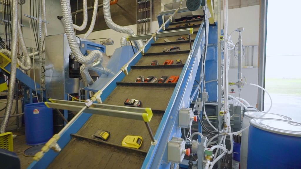 conveyor belt carrying lithium ion batteries into shredder