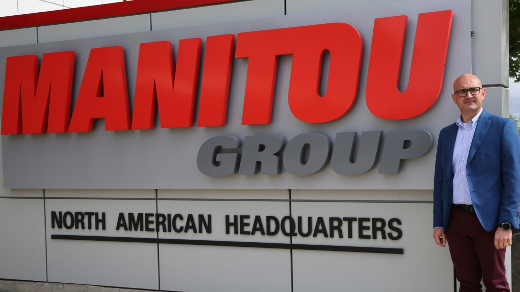 new appointee Ilmars Nartish stands next to Manitou group HQ sign