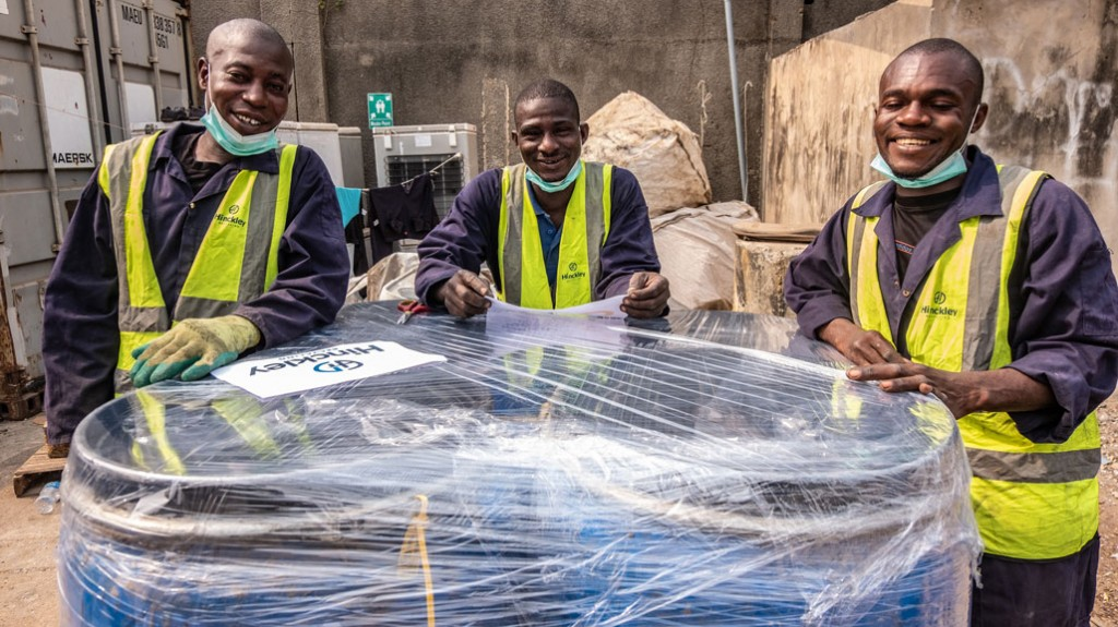 three workers stand in front of a load of wrapped drums