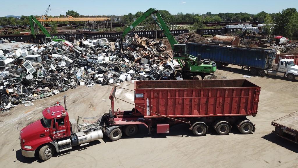 material loader in a scrap yard with a dump truck
