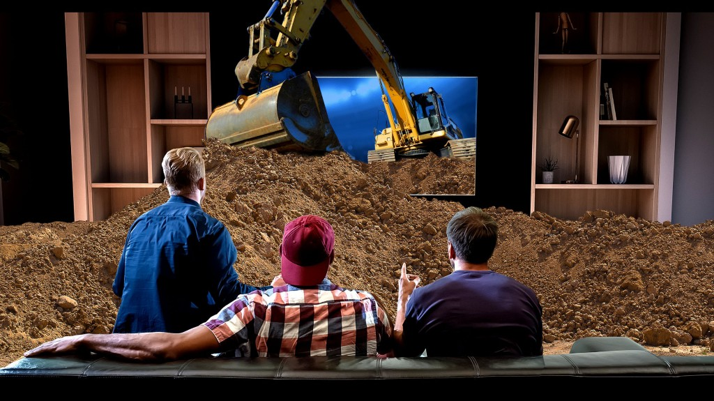 3 men watch a tv screen showing an excavator dig out a pile of dirt