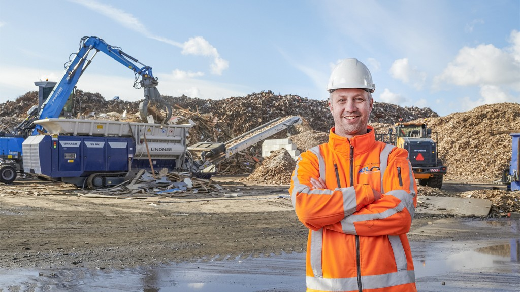 man stands in front of Lindner machine on a worksite