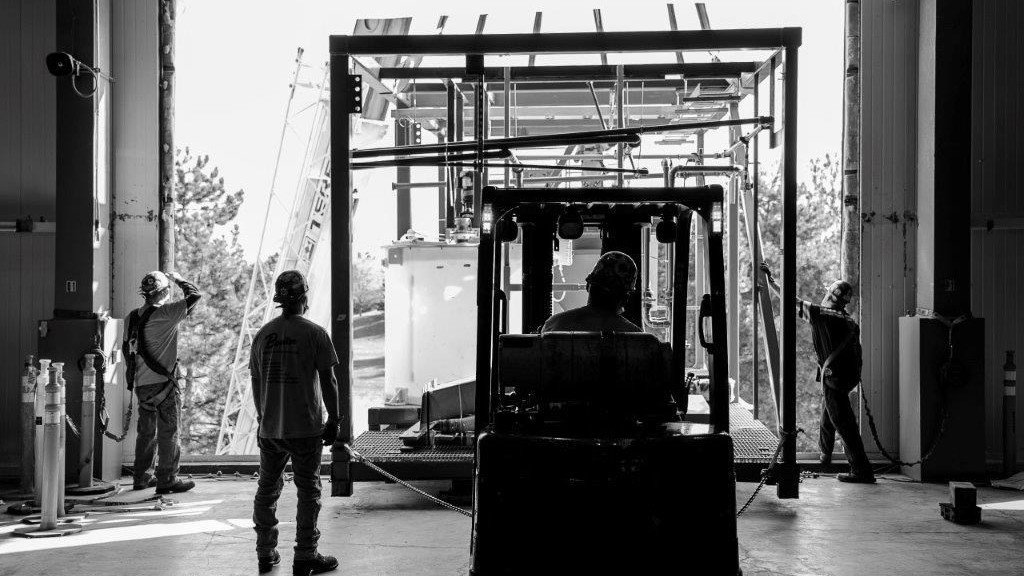 workers watch as a module is being unloaded