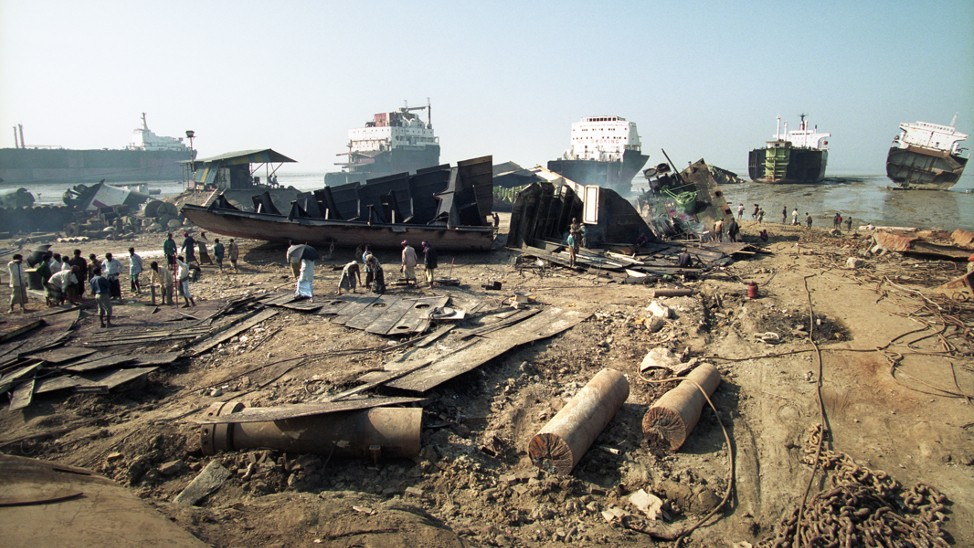 people walk on a beach strewn with rubble and refuse